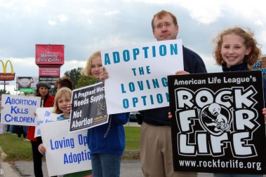 """Rob Fox and his wife Debbie, not pictured, are the parents of six children, including two with special needs. They were horrified when a doctor advised them to abort their youngest child because she was expected to be born with severe health problems, if she was born at all. After much prayer and intercession, the Fox's were blessed with a healthy daughter. The doctor had no explanation as to how the baby survived her dire prognosis. Rob, pictured here with daughters Lauren, Samantha and Kaelyn, says his family prays together and regularly participates in the Life Chain and other pro-life events. """"We come to get the message out that we need to fight for life,"""" he explained. """"We need to get the message out to as many people as we can, and to pray for them."""""""