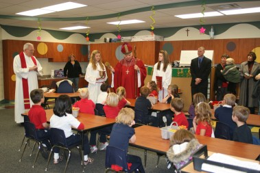 Bishop John M. D'Arcy banters with kindergarten students in one of the four newly constructed classrooms at St. Charles School before blessing the room with holy water on Oct. 14. St. Charles pastor Msgr. John Suelzer, left, and Principal Robert Sordelet, right, are both pleased with the new facility that houses the 84 kindergarten students this year.