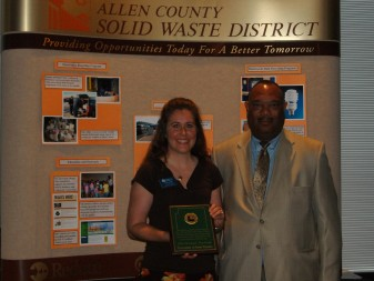 Trina Herber, University of Saint Francis assistant to the dean, stands with Tony Burrus, director of Solid Waste Management. Herber is holding the first place award that USF earned at the Allen County Excellence in Recycling Awards luncheon.