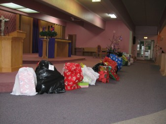 Gifts are placed in the sanctuary of St. Henry Church Dec. 19 at the beginning of a prayer service.