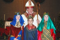Bishop John M. D'Arcy stands with Coley Quinn, William Tiller and Paul Cline, who portrayed the Magi for the feast of the Epiphany at St. Matthew Cathedral on Jan. 3.