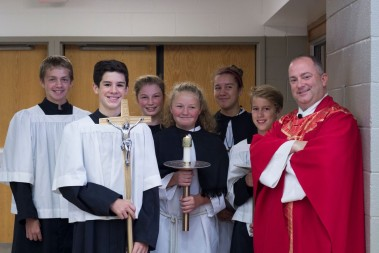 Servers Matt Zollinger, Gavin Dinius, Katherine Heiny, Emma Iehner, Audrey Vasell and Sam Hall, all students at St. John the Baptist, and celebrant Father Andrew Budzinski, gather before Mass at the diocesan confirmation rally Saturday, Oct. 8 at Bishop Dwenger High School.